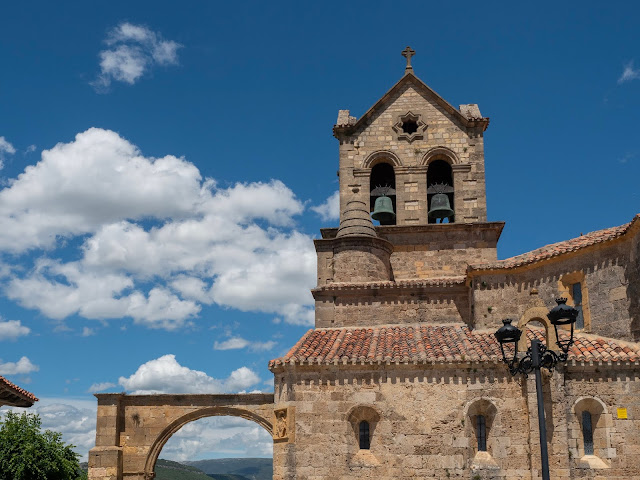 Campanario de iglesia sobre cielo azul con nubes