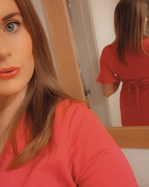 Woman showing off the back of a red dress, in a mirror