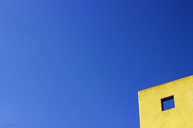 A Lookup Minimalist Photo of a Blue Square within a Yellow Wall.