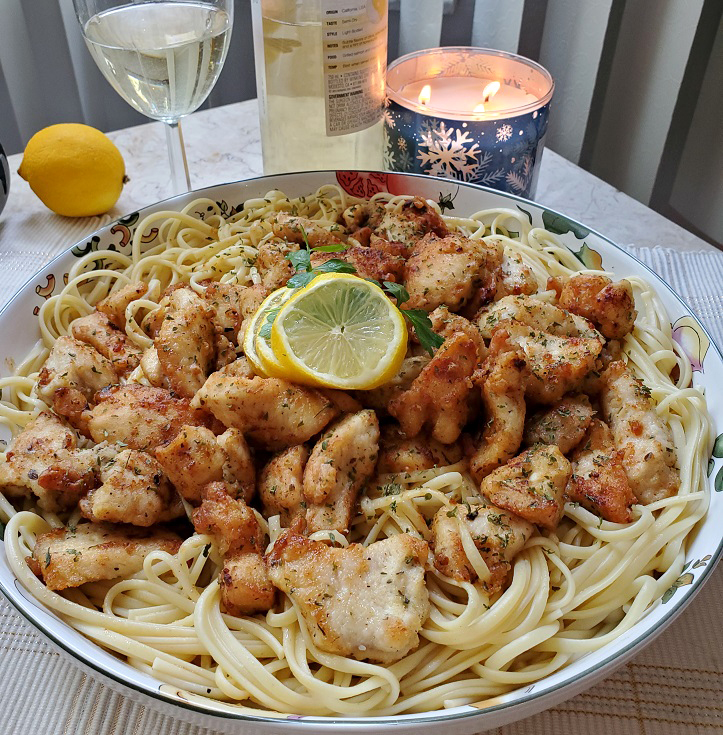 this is an Italian bowl with chicken scampi on top of linguine pasta, a whole lemon and a glass of Pinot Grigio