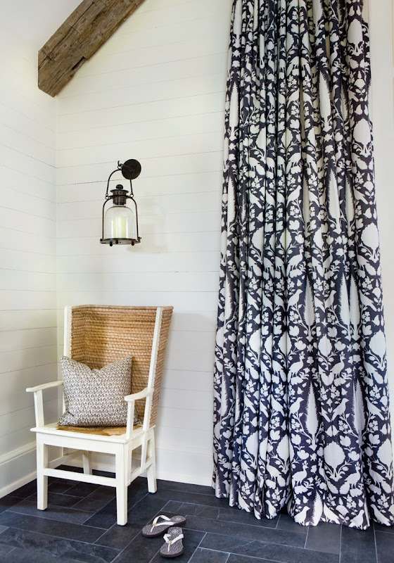 Foyer with navy and white graphic print curtain, stone floor, lantern, visible beams and a high ceiling