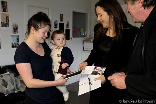 L-R: Rachel Burt, nursery teacher, Cherry Grove Childcare, Havelock North, with daughter Elliot, 11 months; Ailne Bradley, owner, The Dome, Napier; Sam Jackman, president, Havelock North Business Association. presenting a prize to someone affected by the recent gastro outbreak. photograph