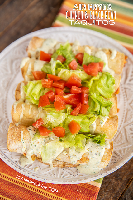 taquitos topped with lettuce and tomatoes on a plate