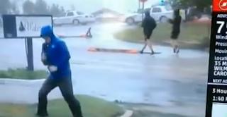 Ρεπόρτερ προσποιείται ότι παλεύει με τυφώνα ενώ πίσω του άνθρωποι περπατούν κανονικά
