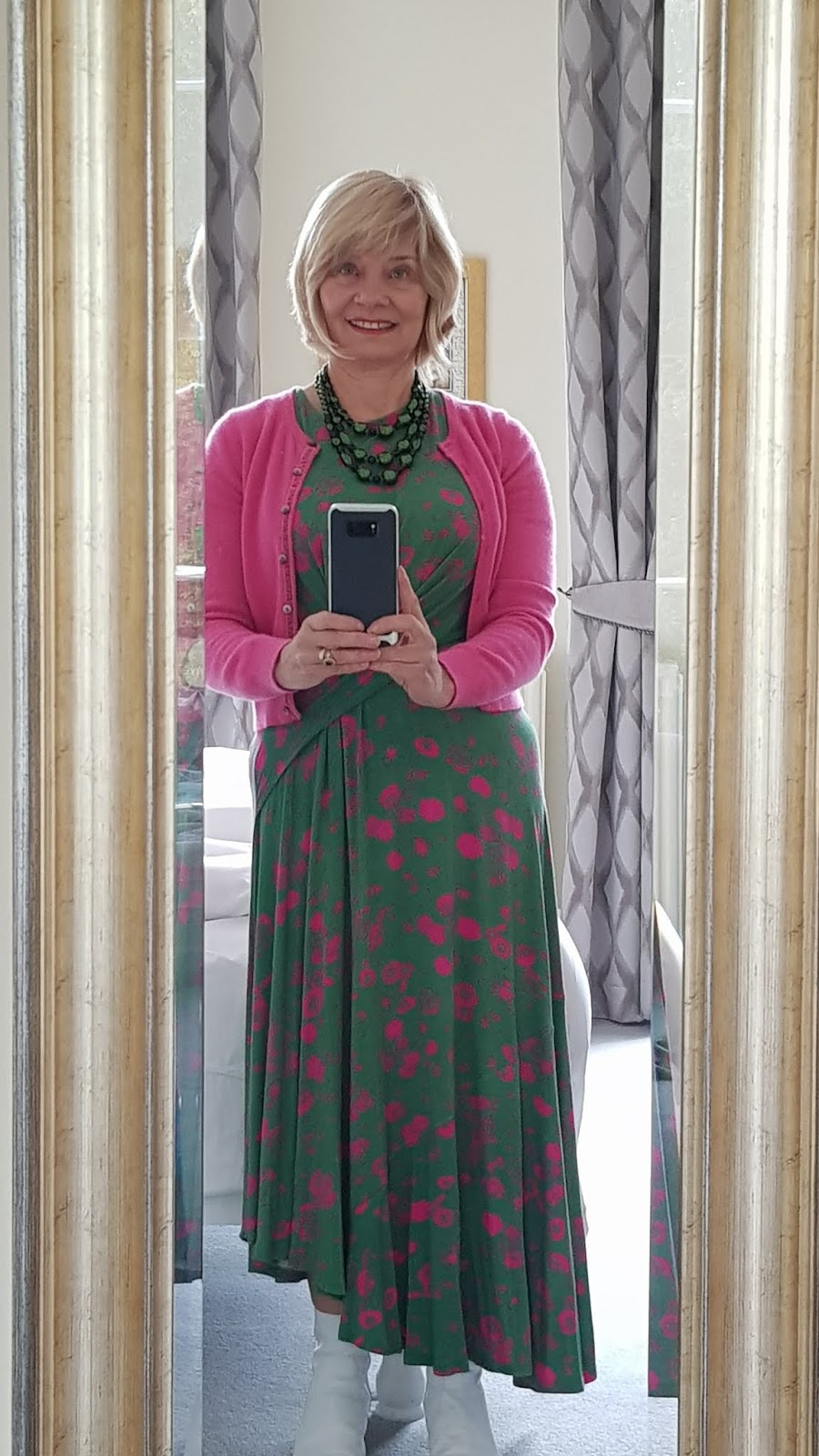 Mid life woman in green and pink midi dress and pink cropped cashmere cardigan.