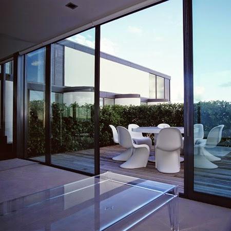 Muro ventana entre una sala y un patio con deck