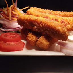 Serving paneer Kurkure in a garnished plate for paneer Kurkure (crispy cheese finger ) recipe