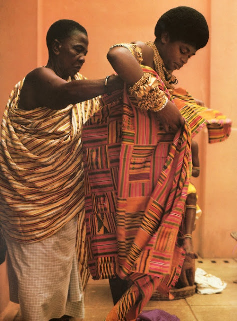 Queen mother being assisted to put on her Kente cloth as tradition and custom demands