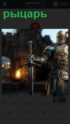 стоит рыцарь в доспехах с мечом в руках на фоне замка