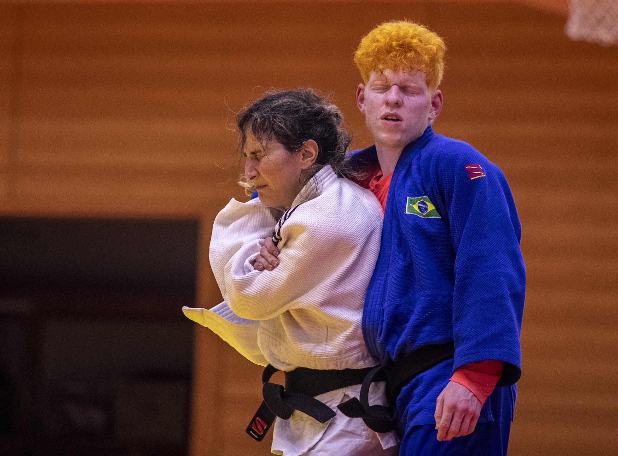 Karla Cardoso e Thiego Marques estão abraçados durante treinamento em Hamamatsu