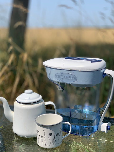 Zerowater filter with enamel teapot and cup on table  in field