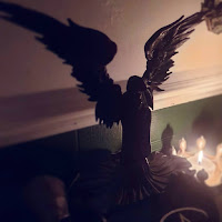 A statue of Badb, made by Nemesis Now. It has large black out-stretched wings, and is wearing a long flowing black robe. It is entirely black. The statue is placed on a stand draped with an altar-cloth that is black with white pentacles. It is against a white wall with green paneling at the bottom and white dado rail. The statue is candle-lit. The image is taken looking from the left across the statue, with the paneling and dado-rail giving an indication of the angle of the wall relative to the camera, as it runs diagonally from the bottom left third of the image to the upper right. The image is square. The points of the crown worn by a resin skull are visible on the far side of the statue.