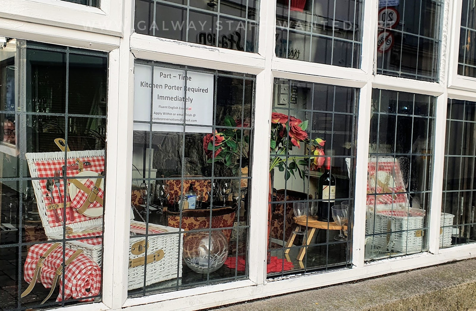 Kitchen porter wanted sign, in a window with a display of picnic baskets with red and white gingham lining and white wicker-work baskets