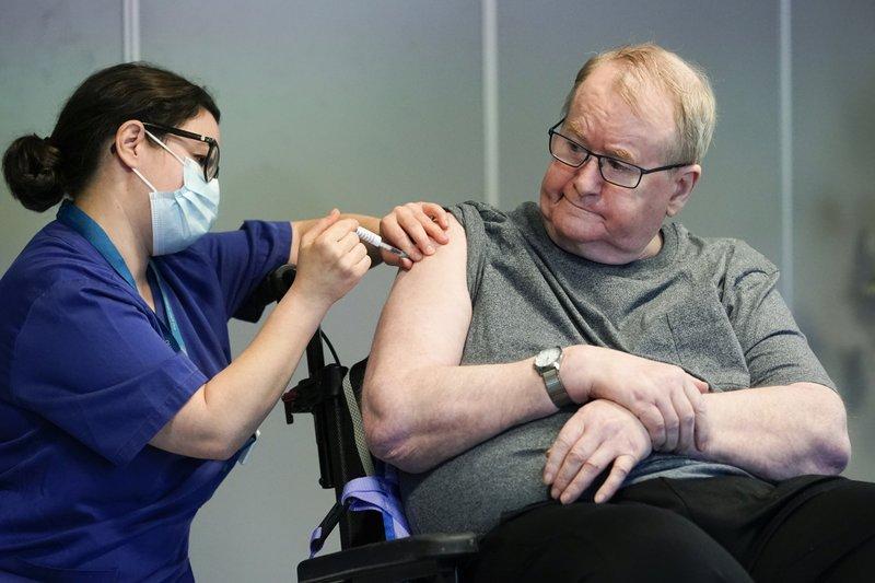 La enfermera Maria Golding vacuna a Svein Andersen, en Oslo, la primera persona en Noruega en recibir la vacuna contra el coronavirus, el 27 de diciembre de 2020. (Fredrik Hagen/NTB via AP)