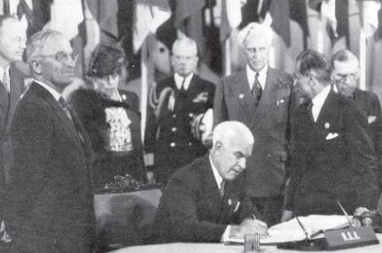 Presiden Harry Truman (kiri) menyaksikan penandatanganan Piagam PBB pada tanggal 26 Juni 1945 di San Fransisco.