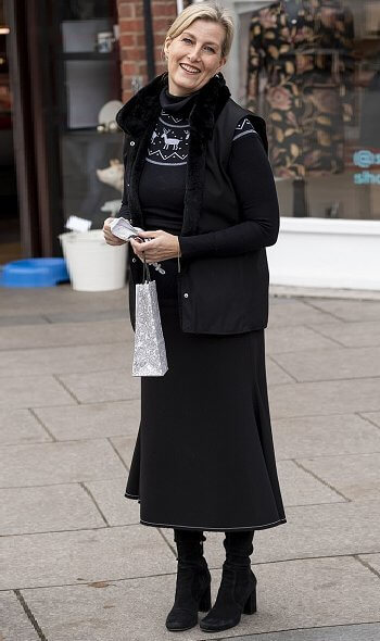 The Countess of Wessex wore a black reindeer-patterned jumper, gilet, and chic long skirt. Patrick Mavros pangolin earrings in sterling silver