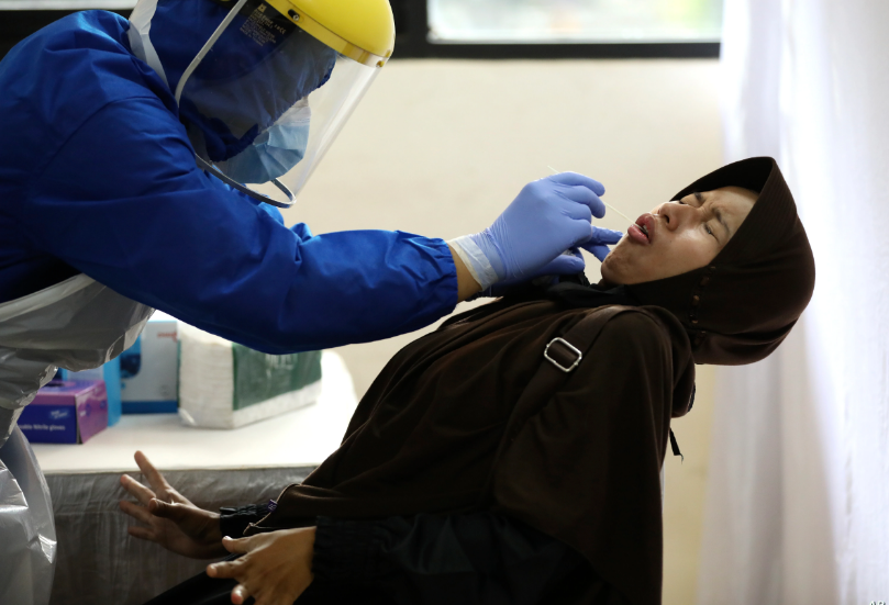 Una mujer reacciona con rechazo a una prueba nasal para el coronavirus en Indonesia, el 21 de junio de 2020 / AP