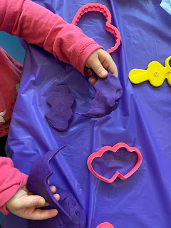 child playing with play dough, making heart shapes