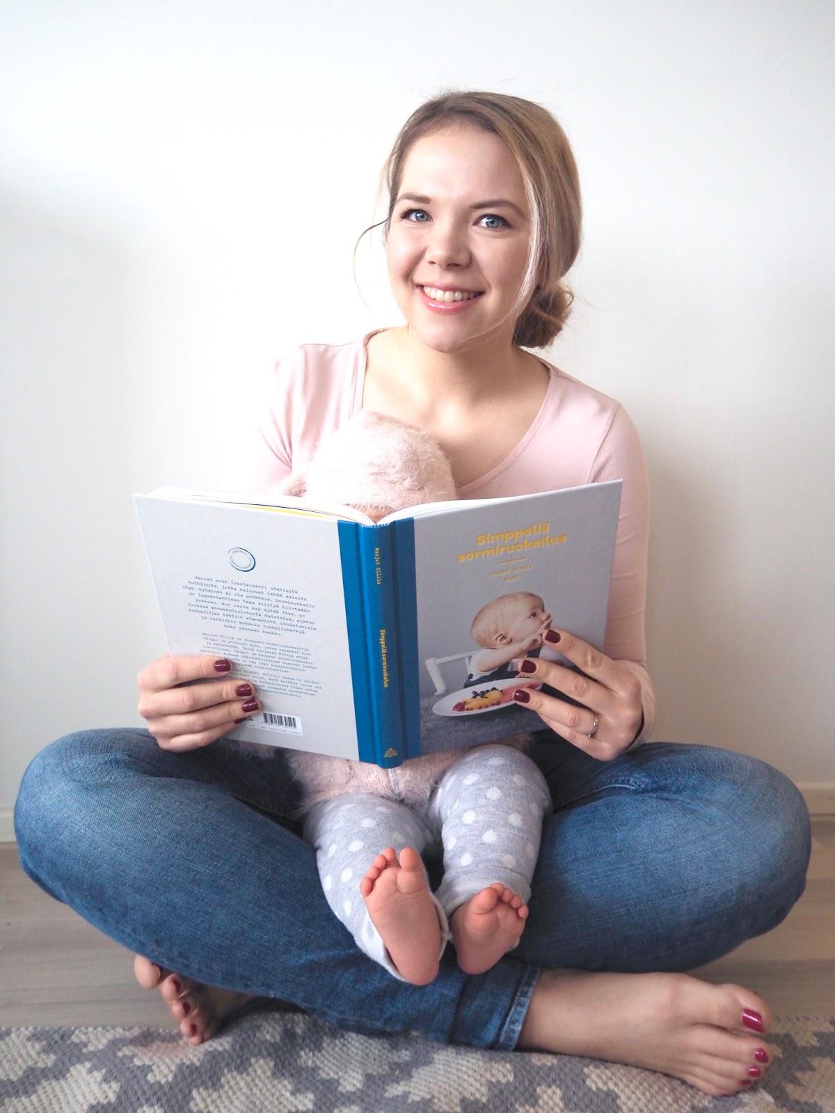 Sormiruokalija selaa Simppeliä Sormiruokailua -kirjaa