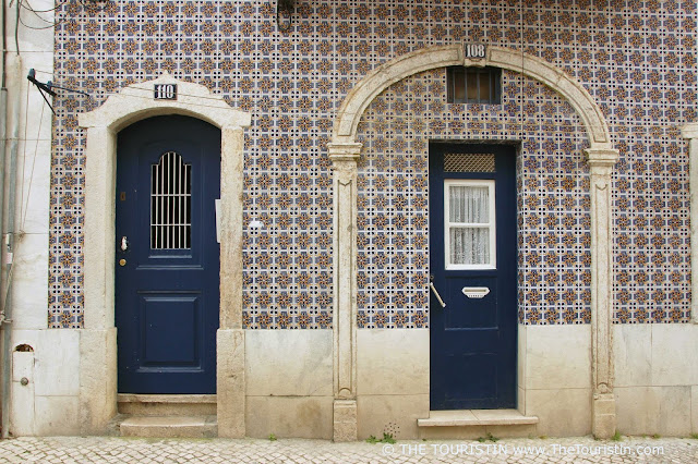 Two dark blue entrance doors of a property with a blue and white tiled facade.