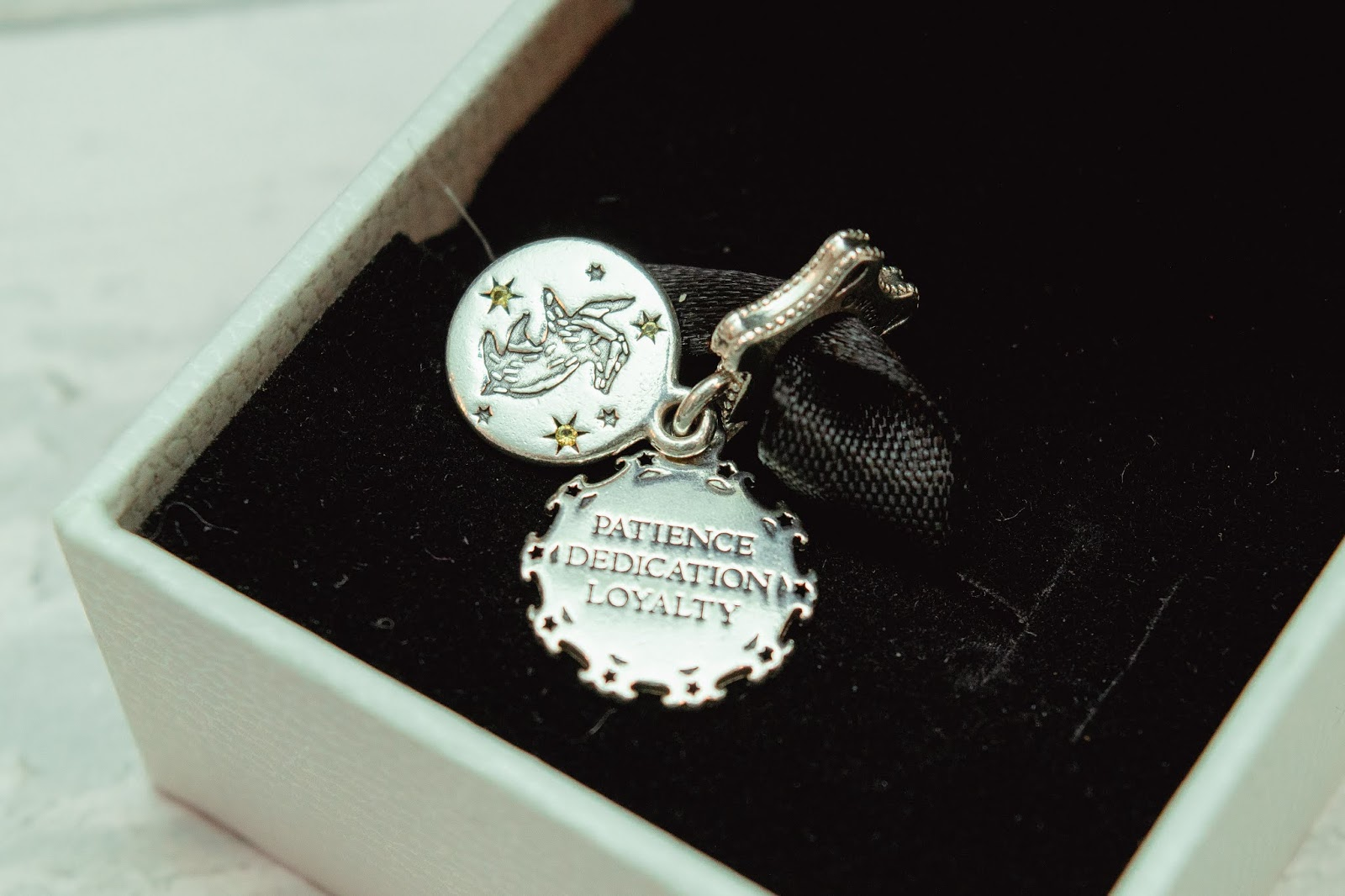 The two parts of the Pandora Hufflepuff charm with the qualities of a Hufflepuff member engraved on a side.