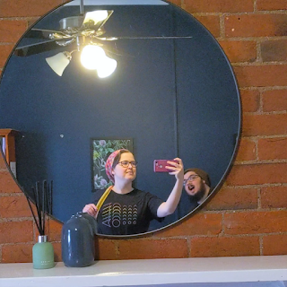 Sarah, a white 30 year old woman, recording video of a mirror over a fireplace with her Google Pixel 3XL in a purple glittery case. Her boyfriend is leaning into frame of the mirror pulling a face.