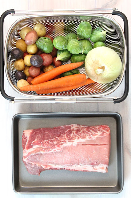 A basket of vegetables next to a baking sheet with uncooked pork loin.