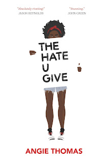 """A Black teenage girl with a red band tying back her hair holds up a white sign with """"THE HATE U GIVE"""" written in black block lettering. """"ANGIE THOMAS"""" is below her feet in red."""