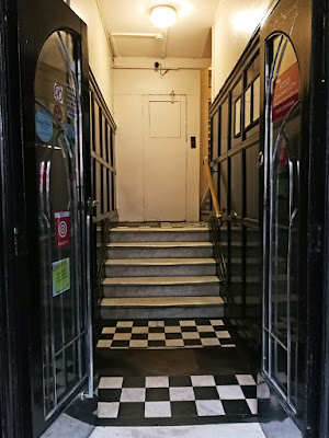 Two black doors with large glass panels are open, leading to a tiled hallway with a short flight of stairs. There is a closed, unmarked door directly ahead; the stairs continue to the right.