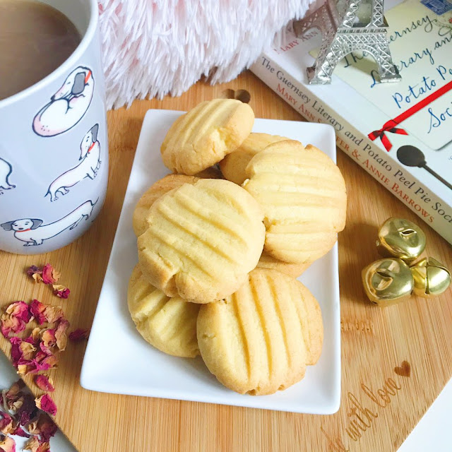 vanilla biscuits on a plate in the centre of heart shaped wooden chopping board. Cup of tea to the left hand side and a book to the right