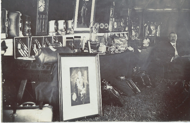 Clocks, knifes, pictures on a table with gentleman seated