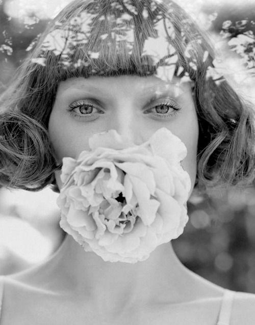 Retrato em preto e branco de uma mulher com uma flor na boca e cabelos curtos estilo anos 20, fotografia de Yu Tsai