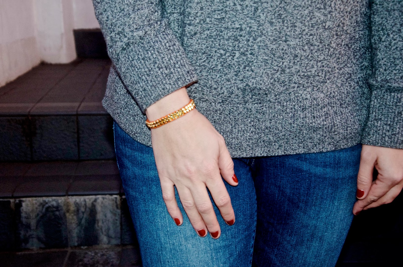 Red nail polish and orange bracelet with gold beads