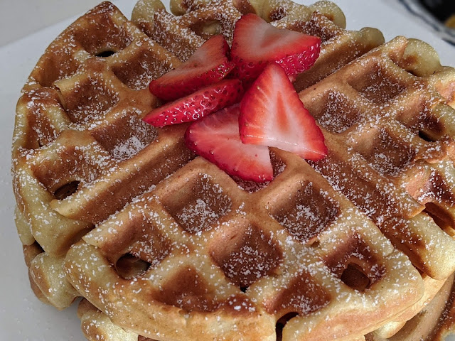waffles with strawberries and powdered sugar