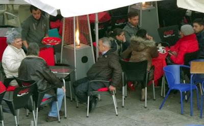pessoas sentadas nas mesas da ribeira com aquecedor