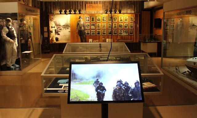 Vitriineitä Rajamuseon näyttelytilassa. Edessä on digitaalinäyttö.