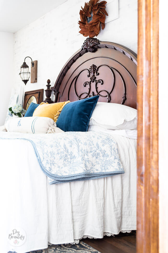 majestic  dark headboard with copper leaves wreath, blue white and yellow bedding