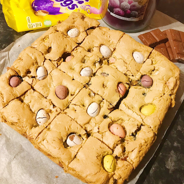 Mini egg cookie slices on baking paper, mini egg wrapper to the left side, home bargains sugared plum candle in the background