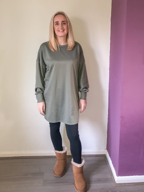 Standing in a khaki green oversize jumper dress with leggings and fluffy boots / winter dresses from Femme Luxe