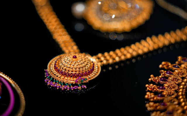 Gold jewelry set displayed on a black surface.
