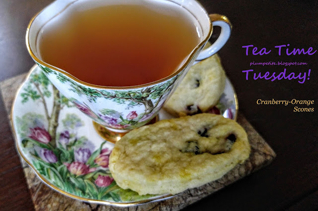 """Image of Antique tea cup and saucer with two cranberry-orange scones surrounding the cup on the saucer.  Has purple and plum text for """"Tea Time Tuesday plumpetite.blogspot.com"""" and a marigold color text for """"Cranberry-Orange Scones"""" on the upper right-hand side of the image."""