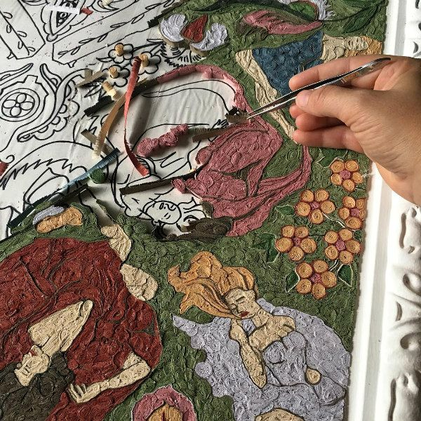 detail of fringed paper rug in progress showing a hand with tweezers placing a papercoil
