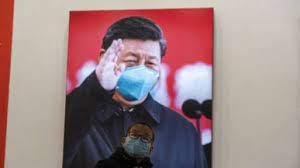 Uma criança usando máscara reage perto de uma foto que mostra o presidente chinês Xi Jinping em uma exposição sobre a luta de Wuhan contra o coronavírus. Esta foto foi tirada em 23 de janeiro de 2021, em Wuhan. AP / Ng Han Guan
