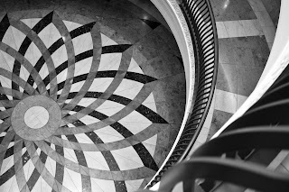 A black and white photograph of a marble floor from the point of view of a second floor interior balcony. The balconies and floor beneath are round, the pattern on the floor an overlapping floral geometric pattern in three shades of marble. The balconies have iron railings and the middle of the floor design is off-centre in the image.