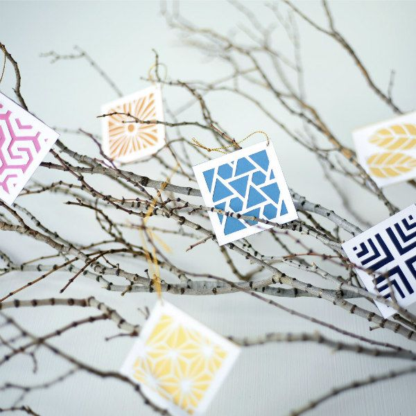 paper cut ornaments hanging on tree branch