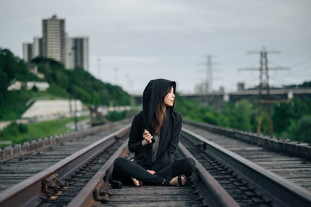 Woman sitting in the middle of train tracks.