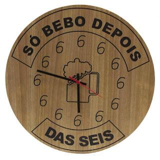 Foto. Em um relógio de parede de madeira clara e redondo. Ao centro, o desenho de uma caneca de chopp com bastante espuma. Os ponteiros marcam treze para às seis. No topo, em semicírculo delineado em preto, um retângulo e dentro lê-se: Só bebo depois. E na parte inferior do relógio: Das seis. Detalhe: a numeração de todas as horas, o número 6, predomina.