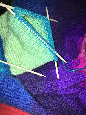 A multicoloured sweater, focusing on the sleeve which is on a set of double-pointed needles.'