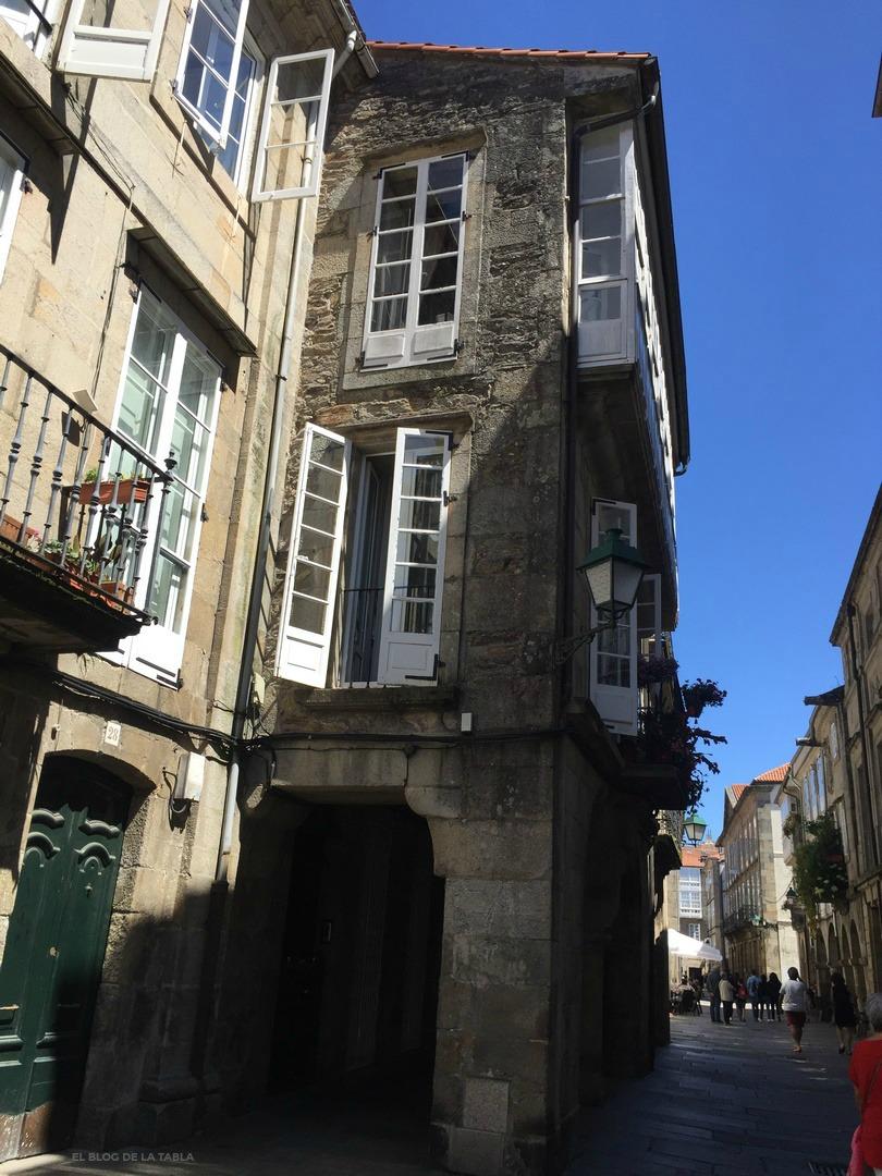 Calle de Santiago con muros piedra, balcones y ventanas blancos