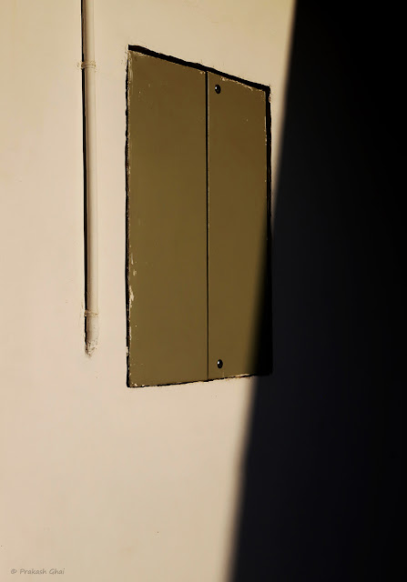 A Minimalist Picture of a Window with a Pipe on one side(line) and shadow on the other.